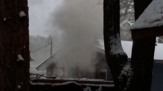 Photo demonstrating a large plume of dark opaque smoke coming from a neighbor's house.