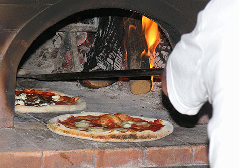 Photo of a chef putting pizzas in an ash-covered wood-burning oven