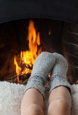Photo: A small child's feet in socks resting near a fireplace in use.