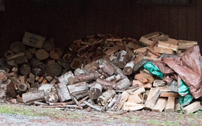 Photo of a woodpile on the ground with a tarp piled on top of it.