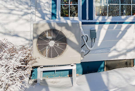 Photo of a heat pump outside a home with snow on the ground.