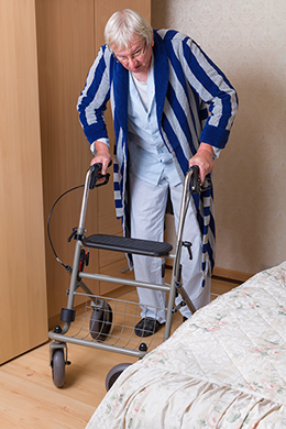 Photo of an elderly man using a walking aid.
