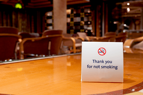 "Photo of a table in a restaurant with a small sign that says ""Thank you for not smoking."""