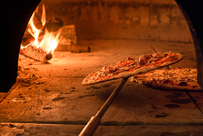 Photo of pizza being cooked in a wood-burning oven.