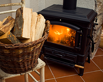 Photo of a wood stove with a basket of logs in front.